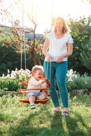 Happy International Children's Day. A young mother having fun with a her happy toddler on a swing. Sunny playground in the backyard. Vertical.