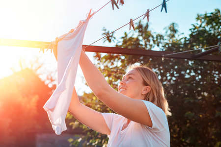A young caucasian smiling woman hanging laundry. 版權商用圖片