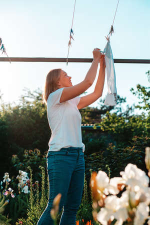 A young caucasian smiling woman hanging laundry. Vertical. Housework.