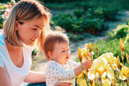 Gardening. Portrait of a caucasian mother and her little child touching yellow iris flowers. Sunny sunset. Summer garden in the backyard. 版權商用圖片