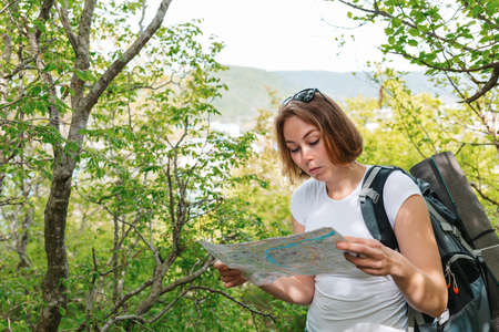 Tourism and active recreation. A young woman with a backpack looks at the map of the area. There is vegetation in the background.
