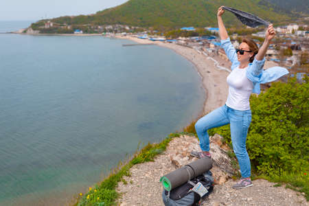 A young tourist woman climbed to the top of the mountain. Emotions of joy and happiness. Mountain and sea in the background. Hiking. Copy space.