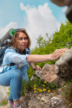 Woman hiker climbing up a rocky mountain path, clutching at the stones. Trees and sky in the background.
