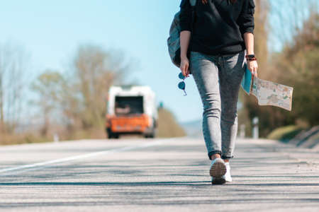 A woman walks along the road with glasses and a paper map in her hands. Car on the background. Legs close-up, bottom view. Copy space. The concept of local hitchhiking.