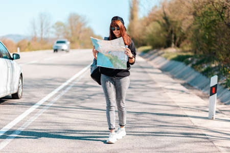 Hitchhiking trips. A young hipster woman in a cap and sunglasses, holding a paper map. In the background, a road with driving cars is blurred. The concept of local travel.
