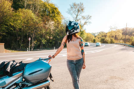 Motorcycle local travel. Young woman with tattoos on her arm, wearing motorcycle gloves and helmet posing near a motorbike. World Motorcyclist Day concept.