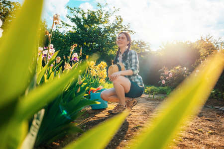 Summer. A young caucasian woman sits in the garden, holding a straw hat. Gardening season. Copy space.