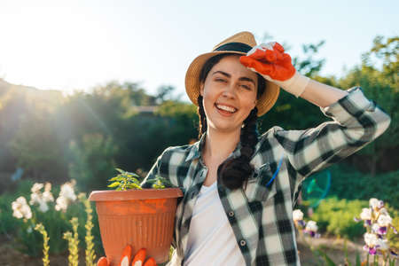 Portrait of a young happy woman in a straw hat holding a pot of seedlings. Outdoor. Earth Day concept.