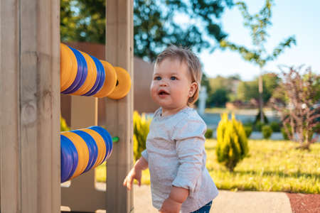 Portrait of a cute Caucasian baby on the playground. Outdoor. Happy children's day. 版權商用圖片