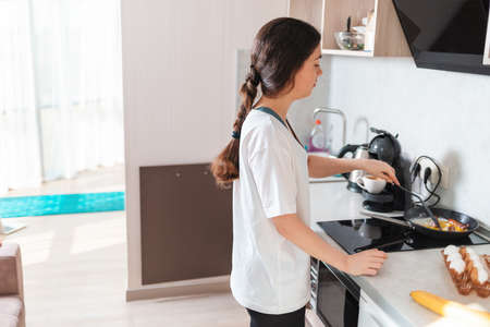 A young woman is frying eggs for breakfast on an induction stove. Side view. Copy space. The concept of a home-cooked meal.