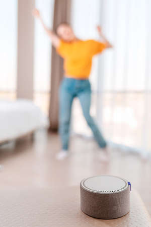A portable smart speaker plays music. In the background, a woman dances in a blur. Vertical. The concept of modern gadgets.
