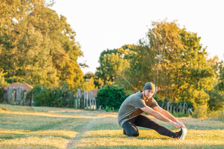 Sports and yoga. A man with a beard, in sportswear doing sports in the Park. Warmup.