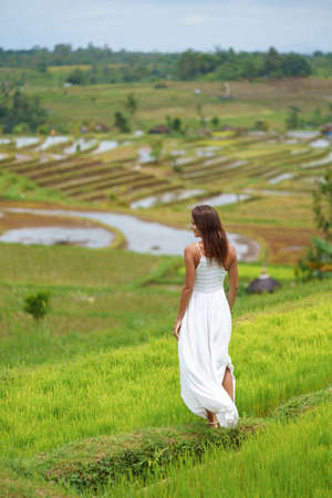 Young woman turning her back posing against the background of rice fields.