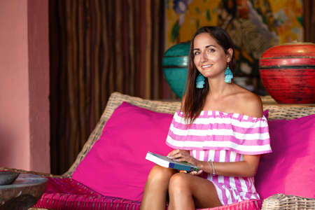 A charming tanned woman sits on a pink sofa with a book in her hands. Posing and smiling. Close up. 版權商用圖片