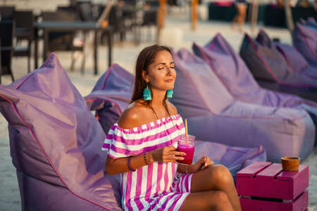 Tanned beautiful girl resting on the beach sofas and drinking a cocktail. Girl smiles and enjoys the sun. Spa and relax concept 版權商用圖片
