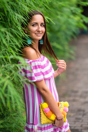 An attractive girl in a striped dress and a handbag in her hands leaned against a green fence.