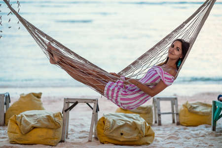 Resort. A young, tanned, beautiful woman in a striped dress is lying on a wicker hammock. Side view. In the background, the sea or ocean. Holidays in tropical countries, relaxing on the beach.
