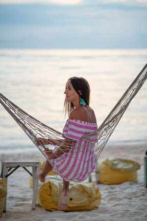 Resort. A young, tanned, beautiful woman in a striped dress poses on a wicker hammock. Rear view. In the background, the sea or ocean. Holidays in tropical countries, relaxing on the beach. Vertical. 版權商用圖片
