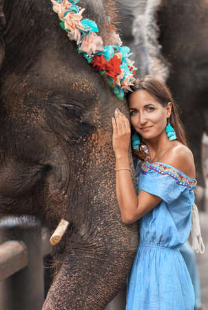 close-up of tanned girl and big elephant together. 版權商用圖片