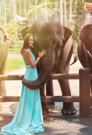 A elegant woman in a turquoise dress and a smile on her face touches a big elephant. Vertical.