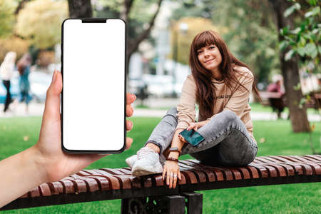 A woman's hand holds a smartphone with a white screen, close-up. A young woman sits on a bench and uses a smartphone. The concept of free wi-fi zone.