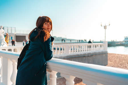 Vacation at the sea. A smiling woman leaning on a balustrade and looking at the camera. Rear view. Cold season.