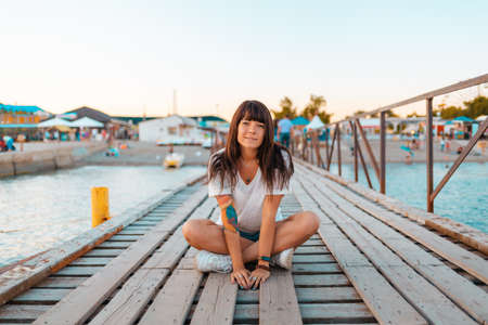A pretty woman with tattoos sits cross-legged on a wooden pier by the sea. The concept of summer vacation.