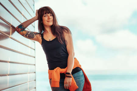 A young beautiful woman with tattoos poses, leaning against a wooden wall. In the background, the sky with clouds and the sea. Copy space. 版權商用圖片