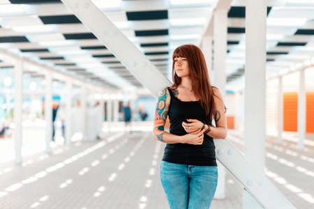 A young beautiful woman with tattoos on her arm, posing, standing near a white staircase. In the background is an architectural perspective. Outdoor.