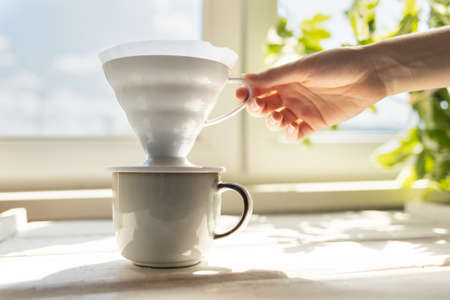 A female's hand removes a funnel with a filter from the cup. Alternative mothod of coffee brewing. Filter V60 with brewed ground coffee. Side view.