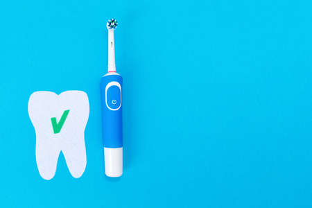 Concept of modern dental care products. Electric toothbrush and a tooth cut out of felt with a green ok icon. Blue background. Flat lay. Copy space. 版權商用圖片