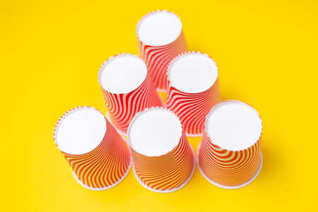 A pyramid of striped red paper cups, on a yellow background. Top view. Close up.