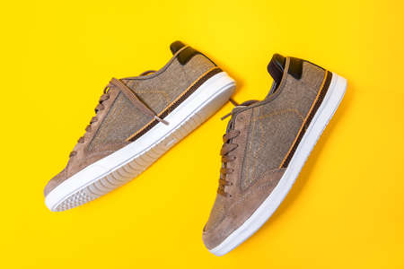 Pair of man's new sneakers made of brown canvas on a yellow background. Side view of shoe. Flat lay.