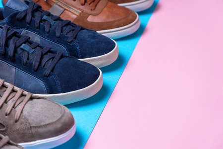 New male's multi-colored sneakers stacked in a row. Shoe tips close-up. Pink and blue background. Close-up. Copy space. The Shoemaker's Holiday concept.