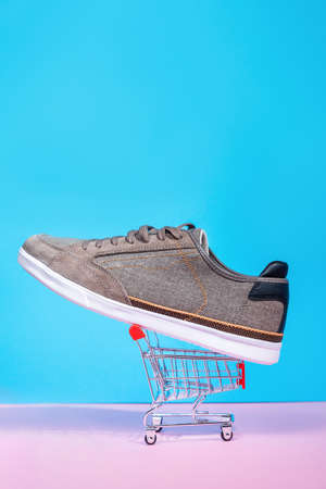 New man's sneaker lies in a small shopping cart on a pink and blue background. Vertical. Copy space. Close up. Shopping concept.