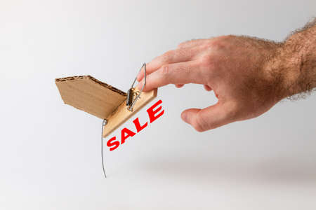 Bank investments and risks. A man's hand caught in a mousetrap with a schematic cardboard house. Copy space. Text SALE.