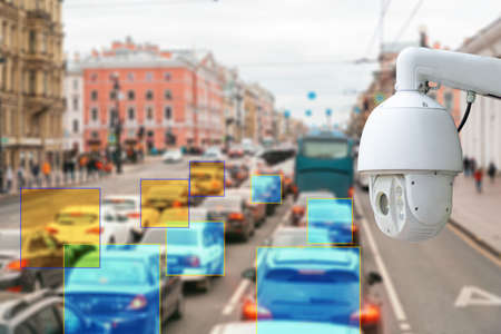 The concept of video surveillance and security technologies. Surveillance camera on the background of the city road with cars. 版權商用圖片