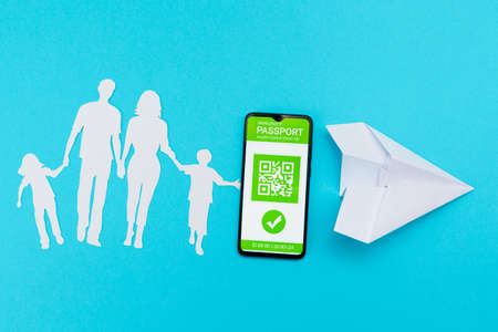 Cellphone with digital immunity passport, paper airplane and a silhouette of a family cut out of paper on a blue background. Concept of vaccination and contemporary travel. Flat lay. 版權商用圖片