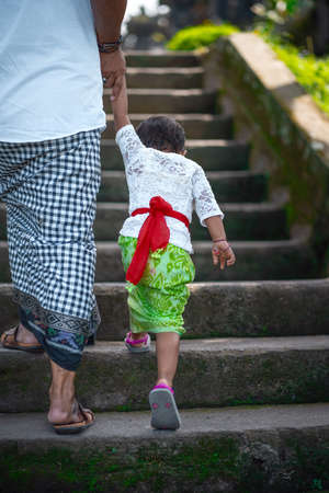 Father and son hold hands and climb the stairs. Indonesian culture. island of Bali. Close up. 版權商用圖片