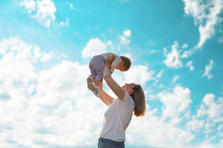 Young happy mother throws up baby in the sky. Side view. Bottom view. Copy space. Concept of happy childhood.