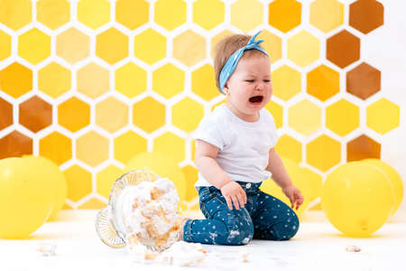 A crying dirty toddler sits next to a broken cake that has fallen to the floor. In the background is a pattern of yellow honeycombs and balloons. Smash cake and birthday concept.