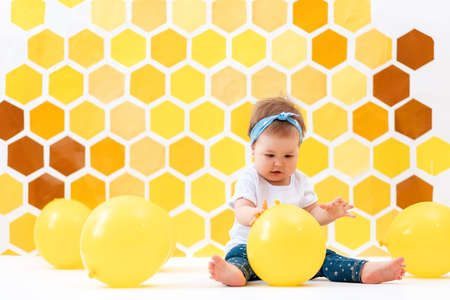 A cute toddler girl is sitting on a white floor and play with yellow balloons. In the background is yellow honeycombs. The concept of the World Children's Day. 版權商用圖片