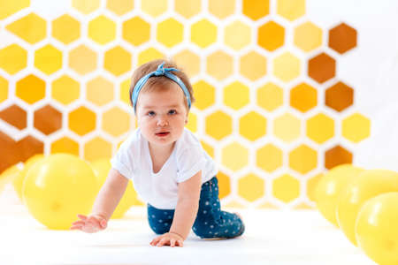 Celebrating. A toddler girl crawling on a white floor with yellow balloons. In the background is yellow honeycombs. Copy space. World Children's Day.