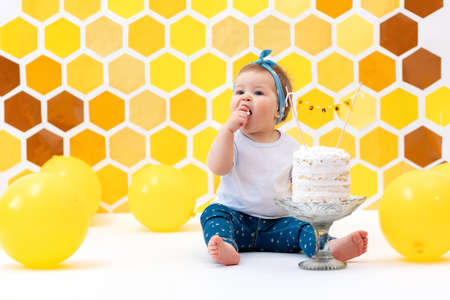 First birthday. A little female toddler sits next to a cake and eats a piece with her hands. In the background, a design of yellow honeycombs and balloons. Smash cake concept. 版權商用圖片