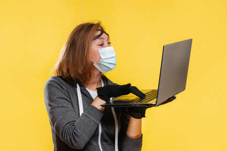 The new normal. A female hacker in a black hat, gloves and a protective mask holds a laptop in her hands, trying to hack it. Yellow background. The concept of cybercrime. 版權商用圖片