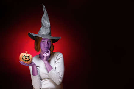Halloween. A young woman with purple skin in a black witch hat is holding a pumpkin with a zombie face. Dark red background and copy space.