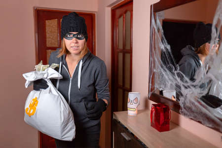 A woman in a robber's costume, holding a bag of money and looking scared. On the wall is a mirror with a web on the frame. The concept of Halloween and holiday.