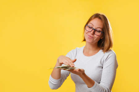 Portrait of a young contented woman wasting money. Yellow background. Copy space. The concept of success and wealth.