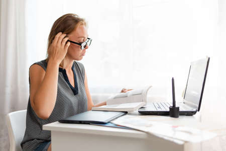Office work, freelance and business. A young blonde woman, thoughtfully reading a book with glasses and working with a computer. 版權商用圖片
