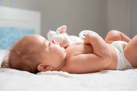 A baby is lying with a toy in the cradle. Close-up. The concept of parenthood.